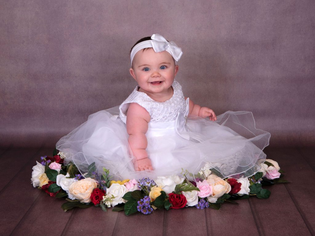 Little toddler in a christening dress surrounded by flowers