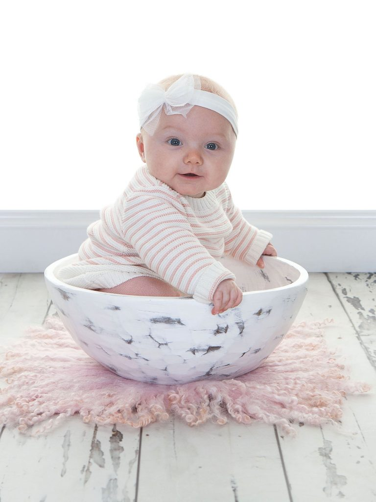 Toddler wearing a white bow in her hair sat in an ornamental white bowl