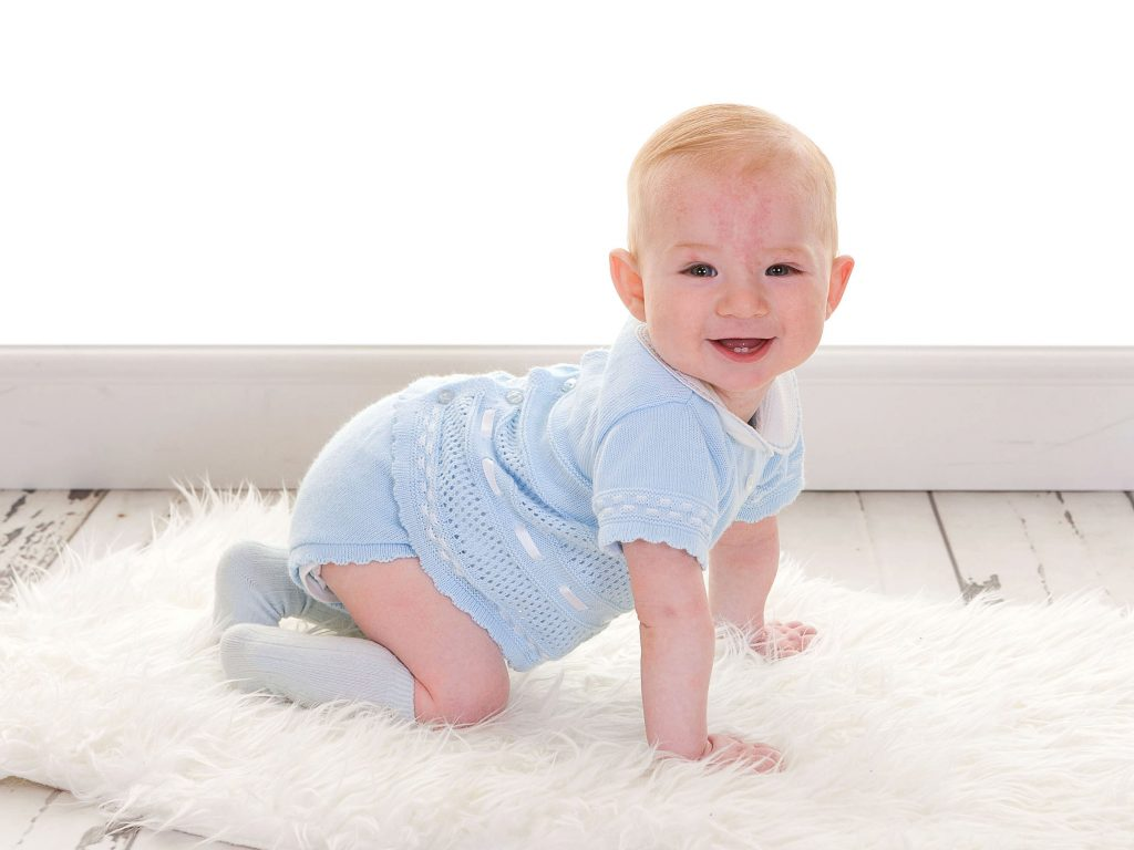 Toddler with a lovely blue top on crawling