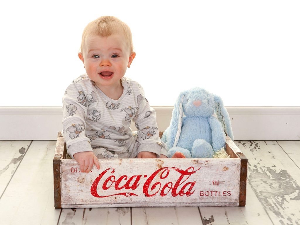 Toddler sat in a Coca Cola crate with a blue toy bunny rabbit