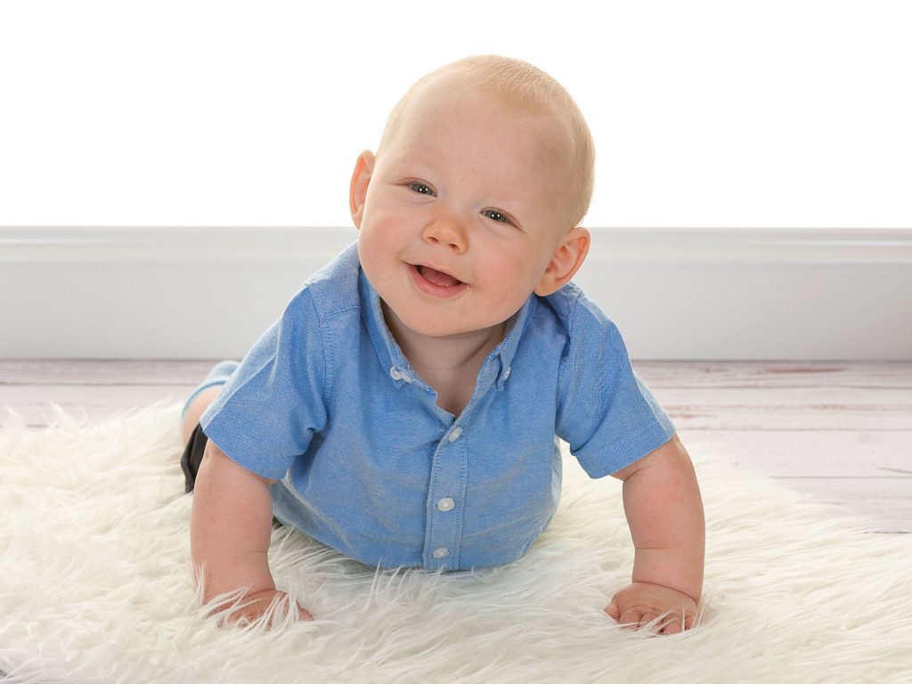 Toddler wearing a blue shirt looking at the camera while lying belly down on a rug