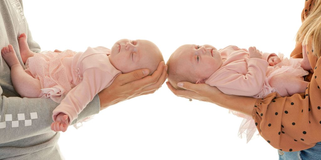 twin newborns asleep in mom and dad's arms