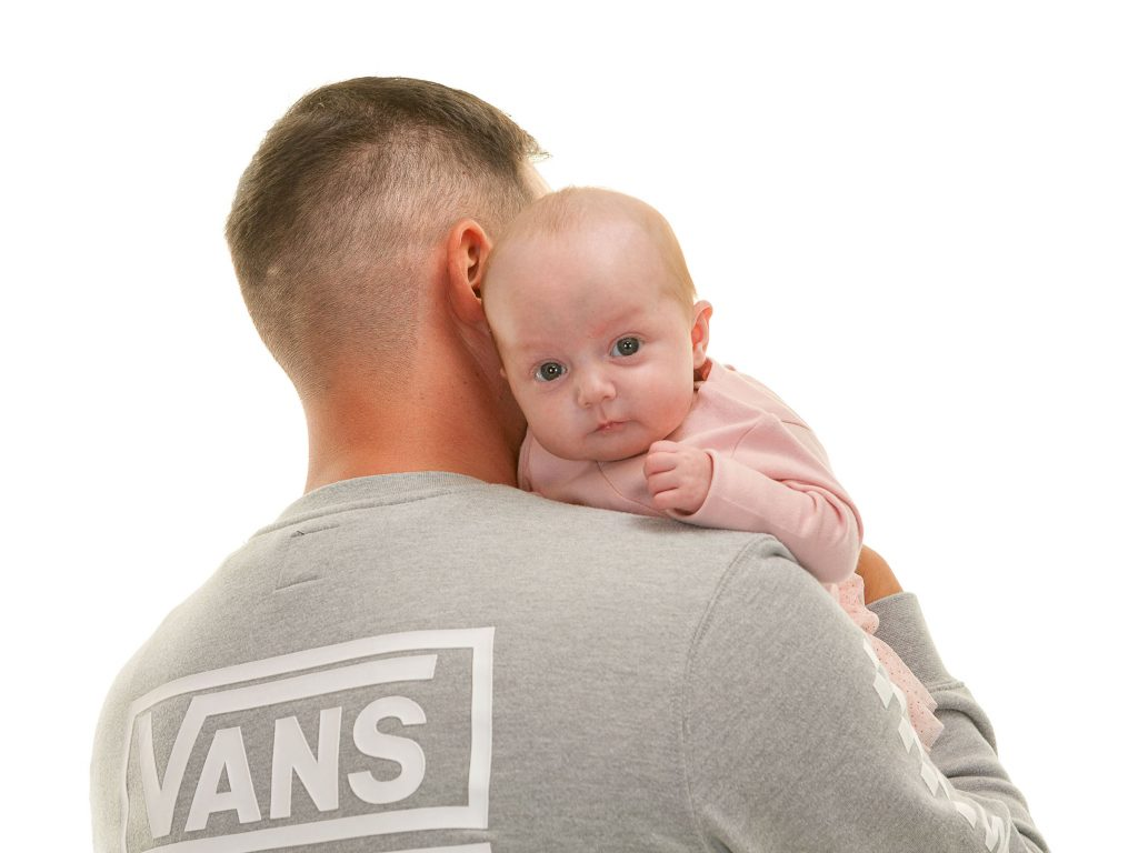 dad's back to the camera with newborn baby looking at you