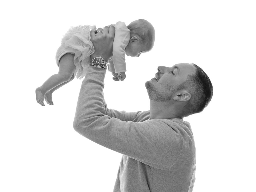 dad lifts his newborn baby above his head in elation