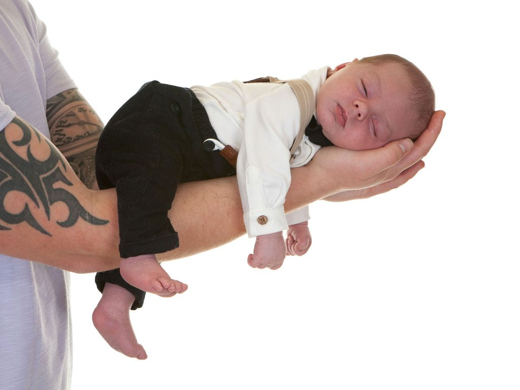 newborn baby sleeps with arms and legs dangling down