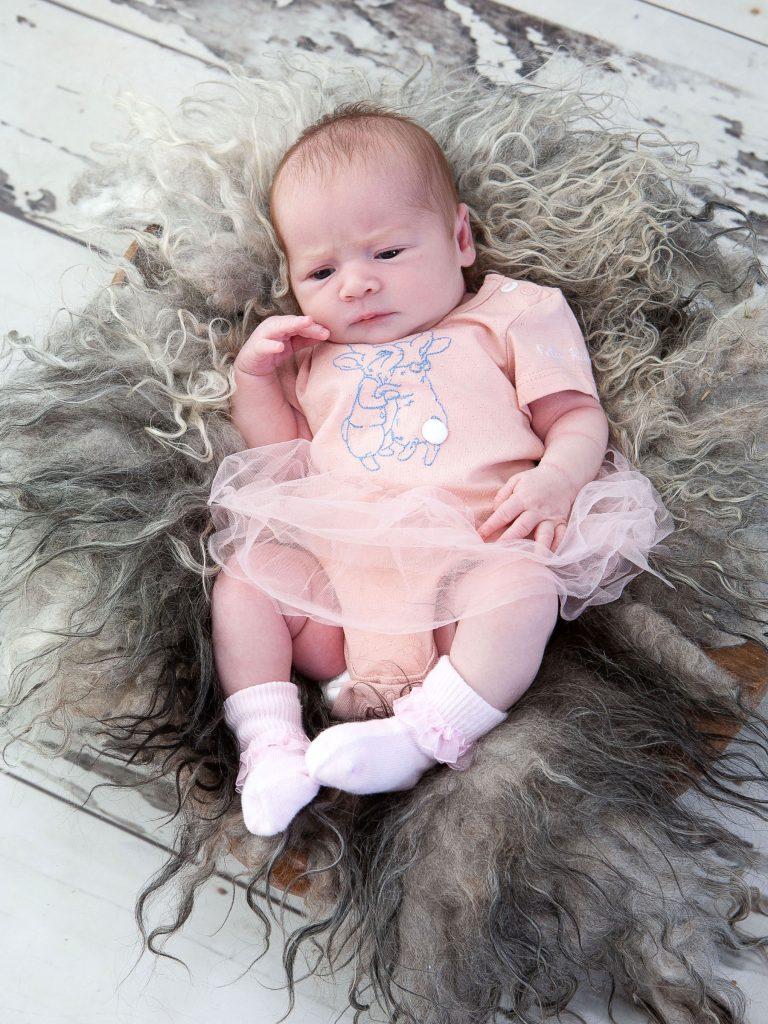 newborn girl awake in pink tutu