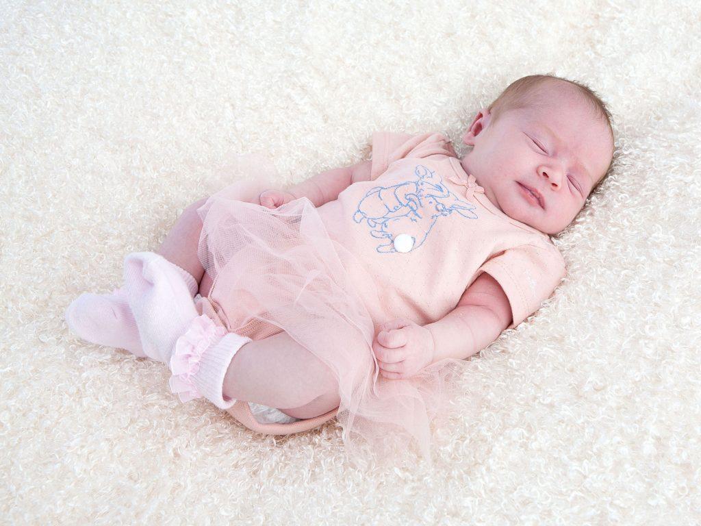 sleeping newborn in peach dress with tutu