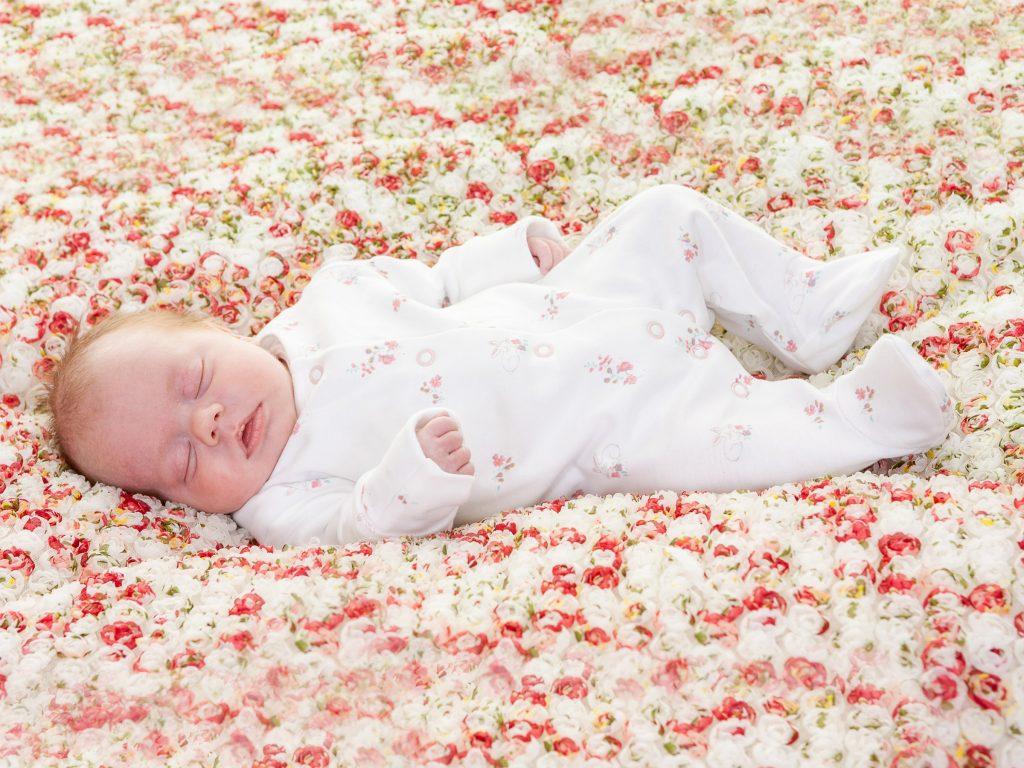little newborn girl lying in a textured blanket