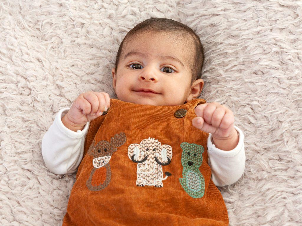newborn baby with with orange dungarees