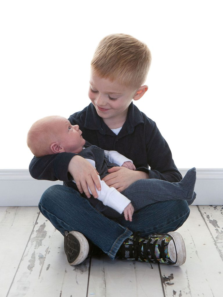 newborn baby boy being held by his older brother