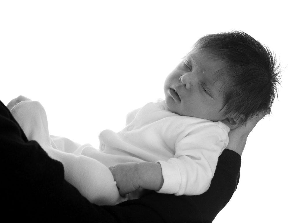 newborn baby girl sleeping in her mom's arms