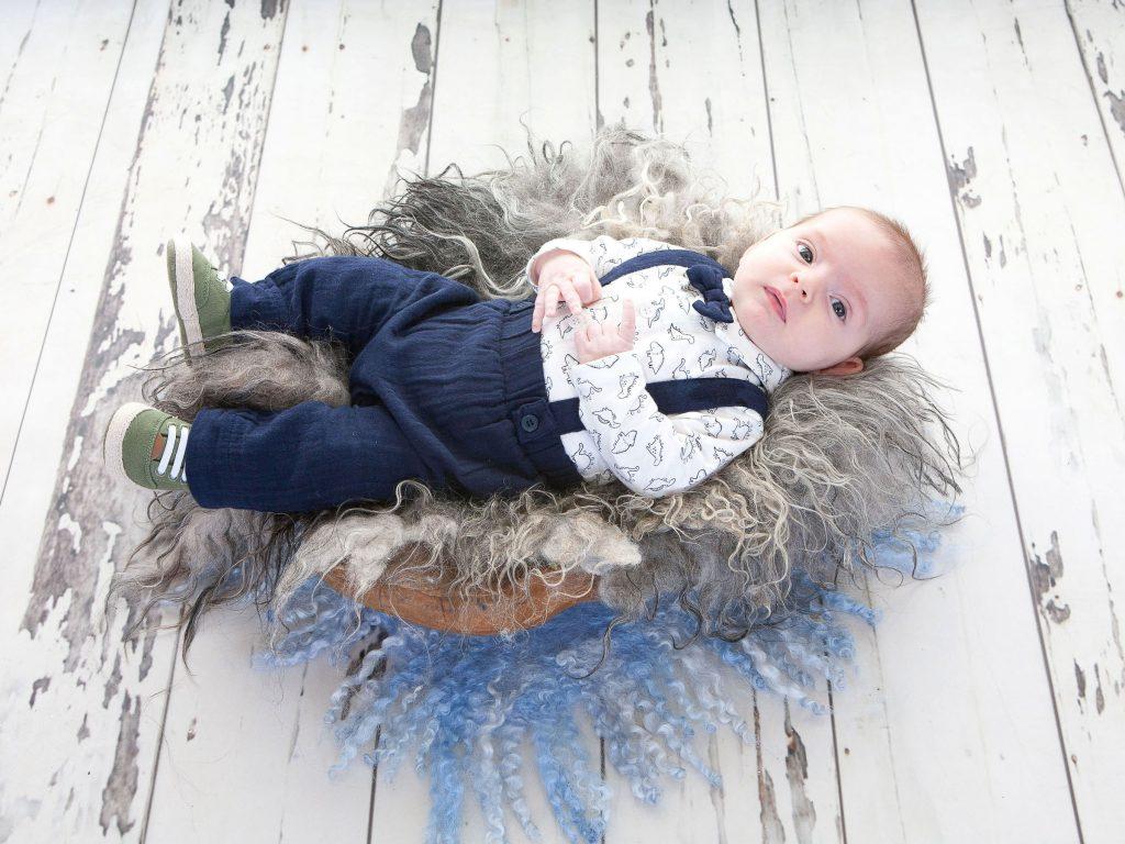 newborn baby boy lying on a rug