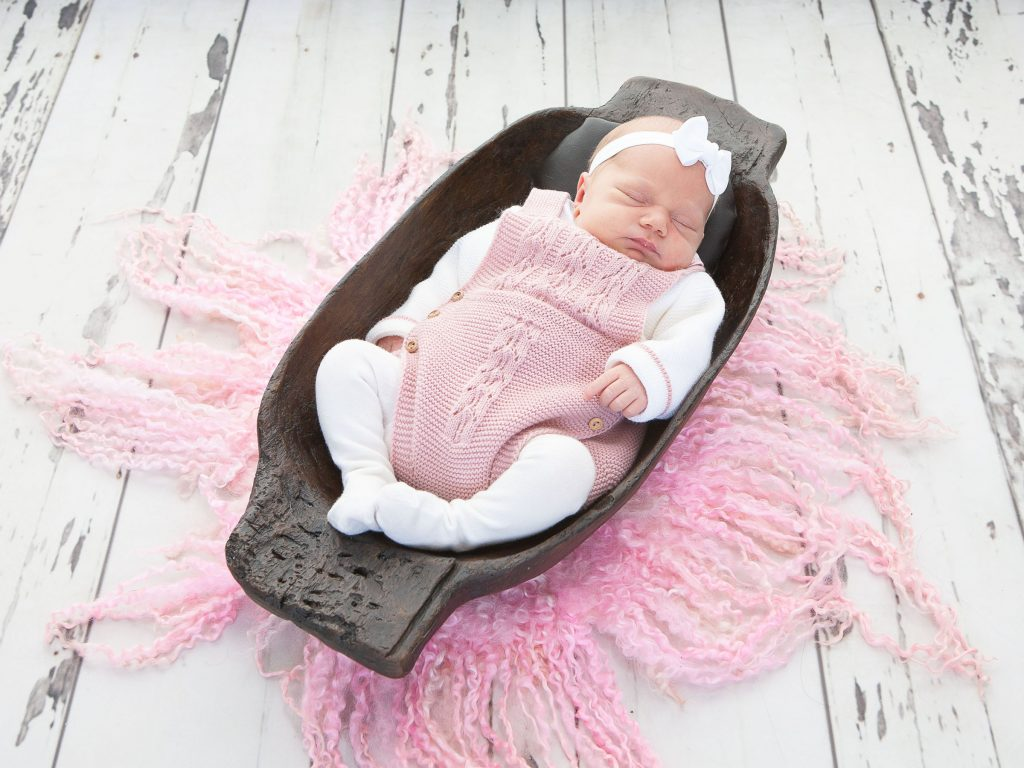 newborn baby girl in a wooden bowl
