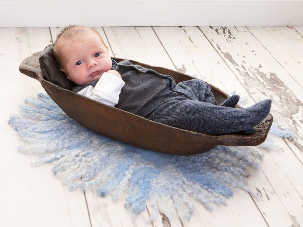 little newborn baby in long wooden bowl