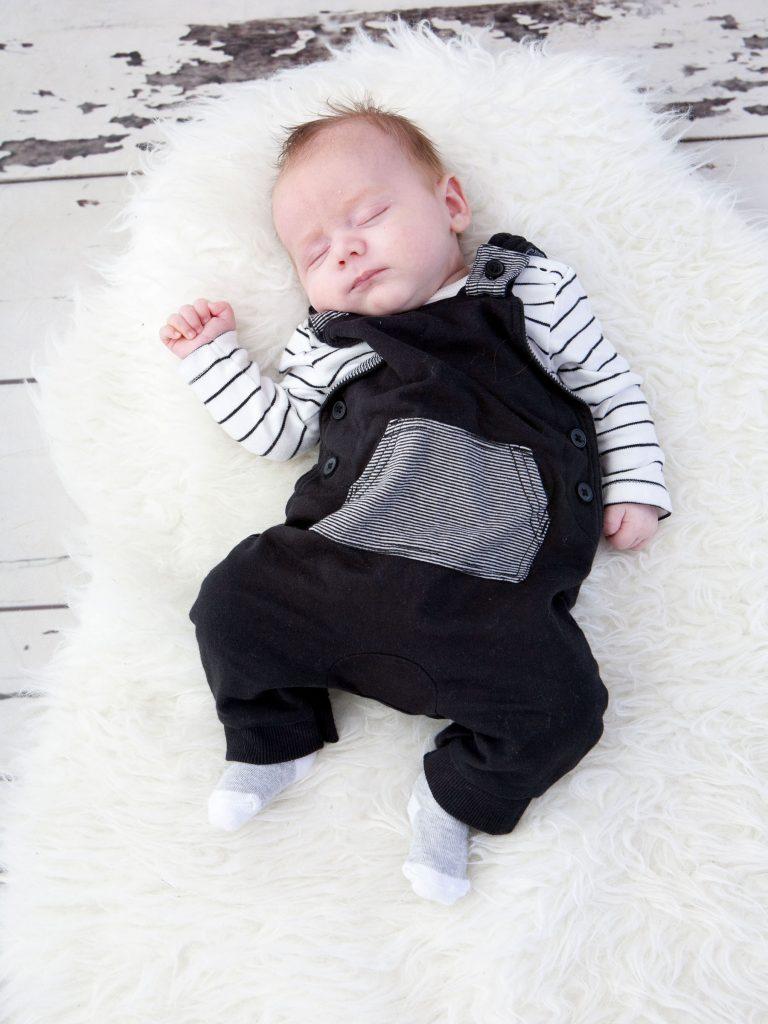 newborn baby sleeping on sheep skin rug