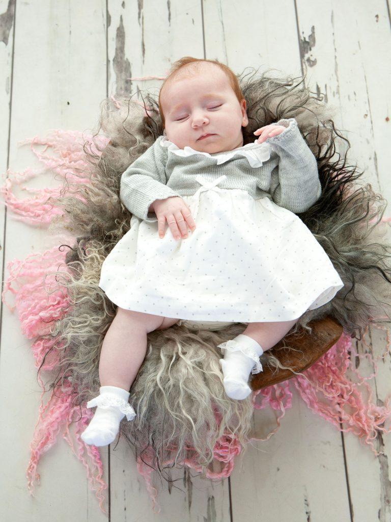 little newborn girl sleeps on a textured rug