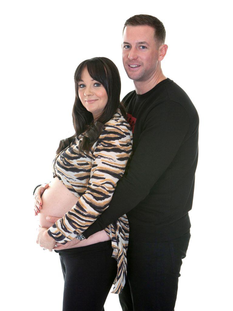 father and mother cup her pregnant belly