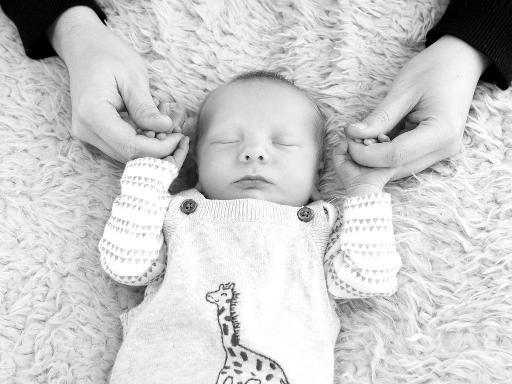 Black and white photo of a baby asleep with their parent holding their hands
