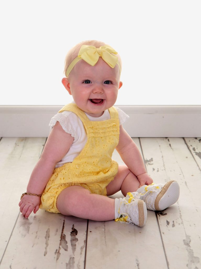 Little toddler with a yellow bow and a yellow dress