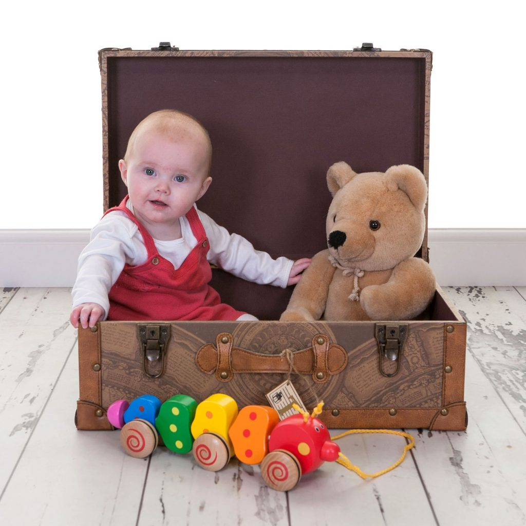 Toddler baby sat in an open chest case with a teddy bear