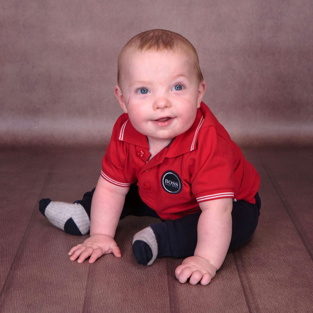 Lovely toddler wearing a red boss polo shirt