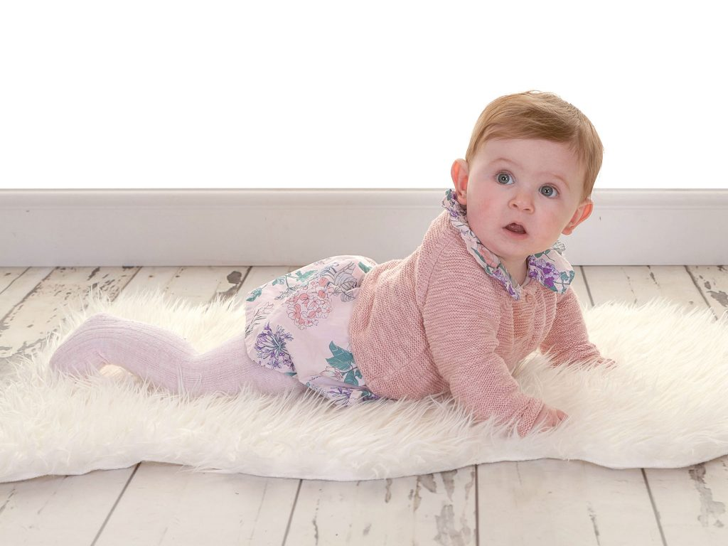 toddler wearing pink cardigan and a floral dress lying on a textured rug