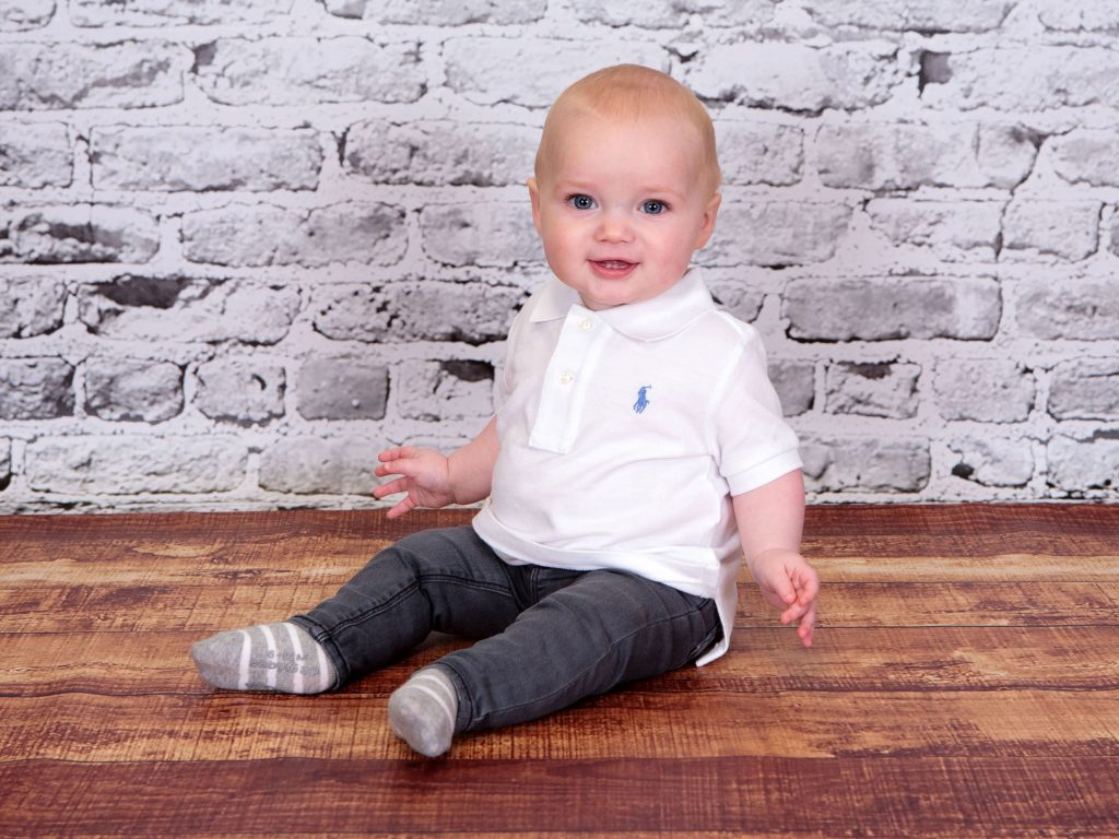 Toddler sat upright wearing denim jeans and polo shirt