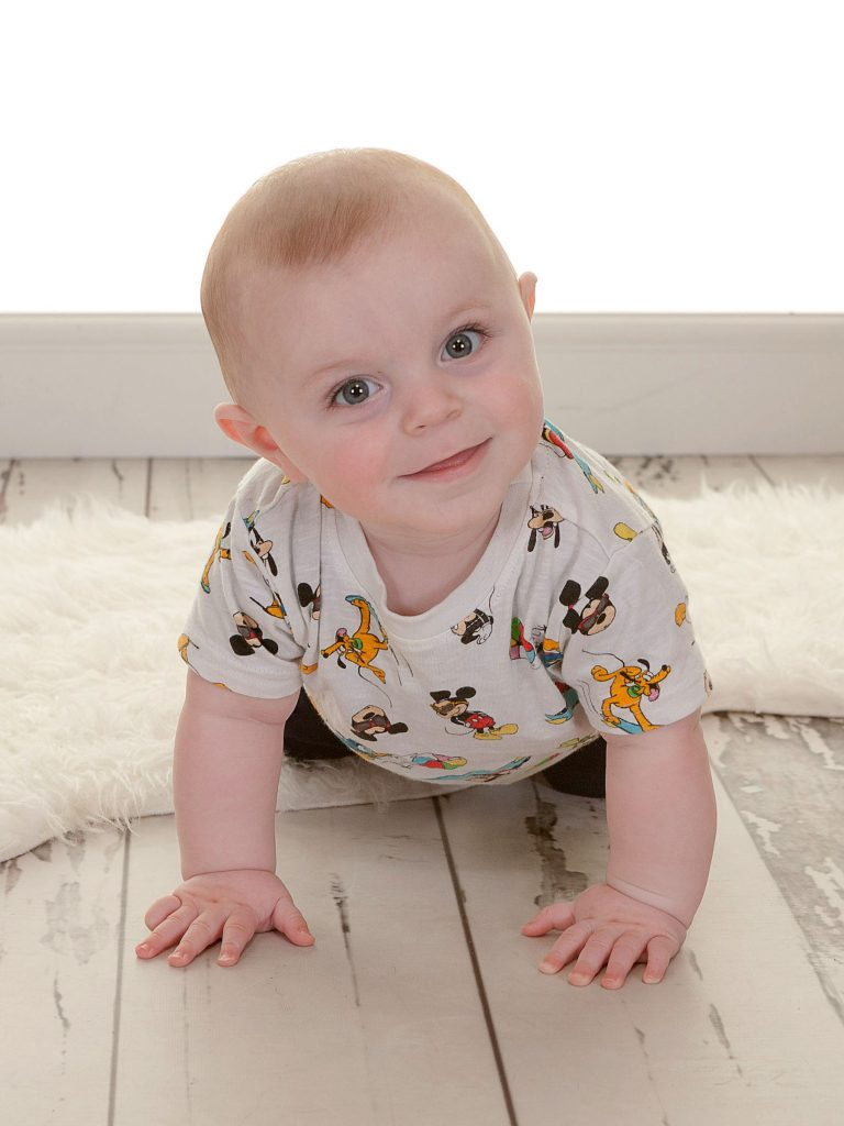 Toddler looking at camera on all fours