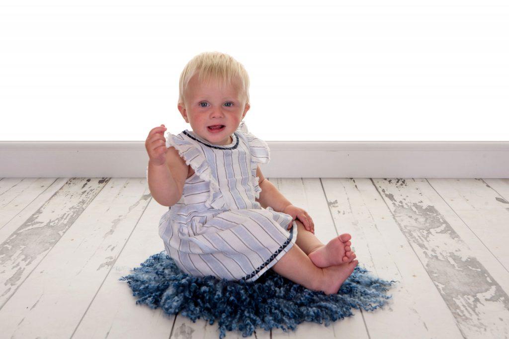 Toddler sat on a blu textured rug