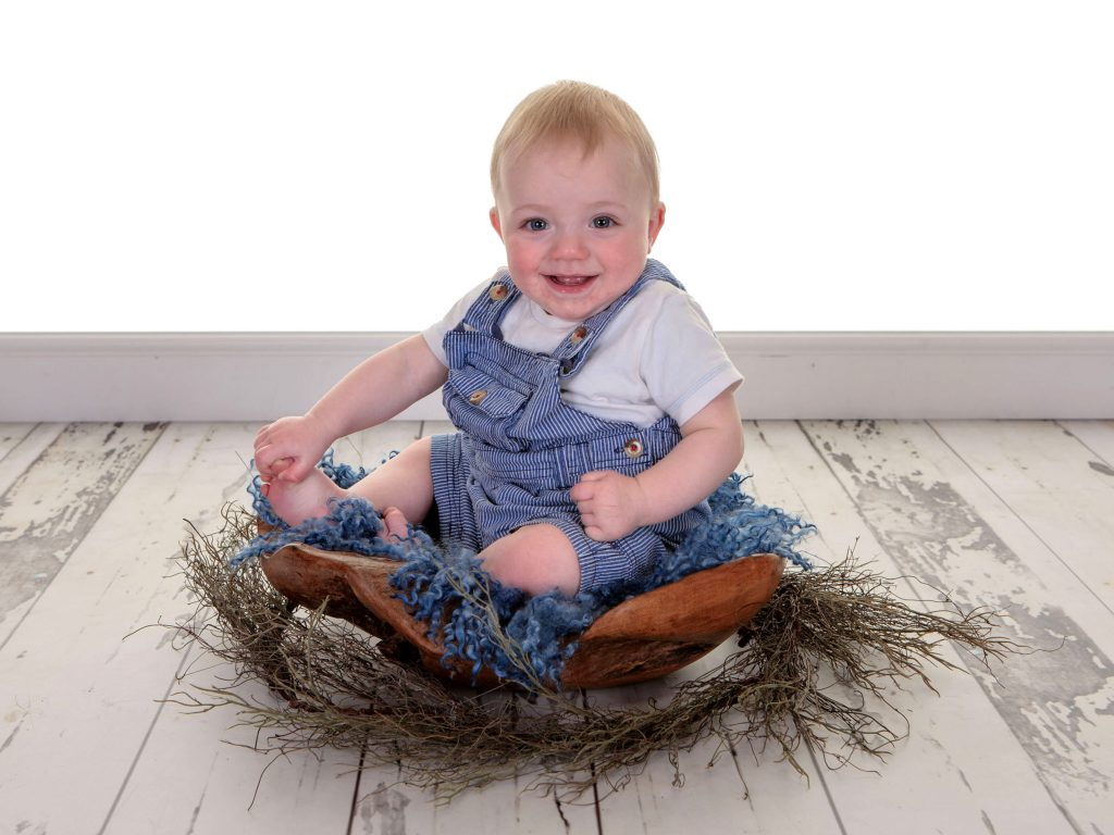 Little toddler sat up in a wooden bowl prop