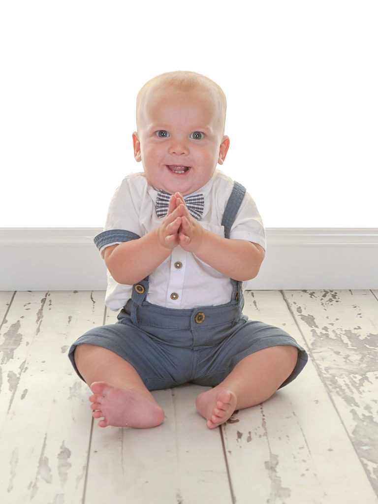 Little boy toddler sat up clapping his hands