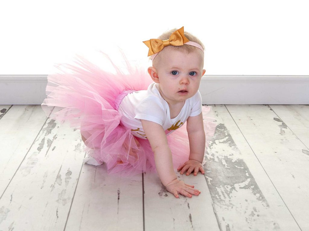 Little girl with a golden bow in her hair wearing a tutu