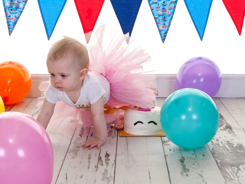 Little girl wearing a tutu crawling away from her first birthday cake