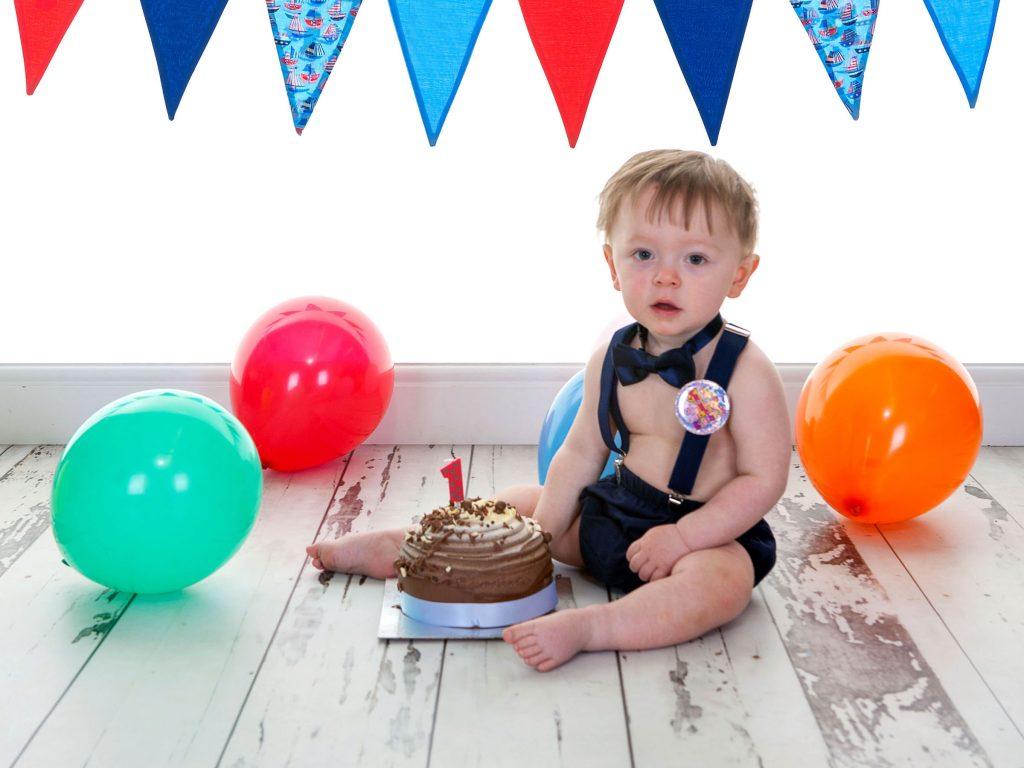Little boy sat next to his first birthday cake