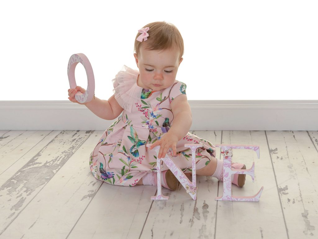 Little girl with a pink bow in her hair playing with a photoshoot prop