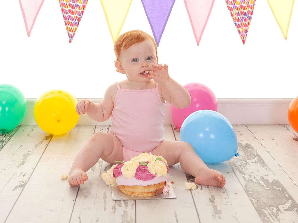 Little baby girl with ginger hair eating her first birthday cake