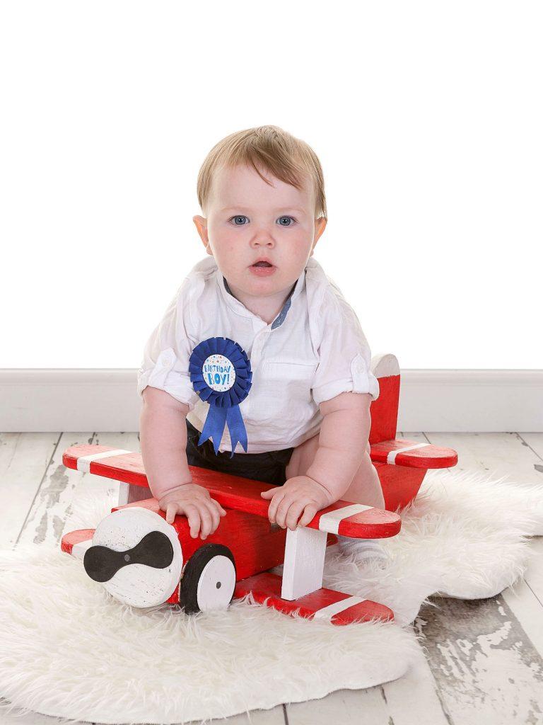 little boy enjoying his first birthday shoot sat on a red plane