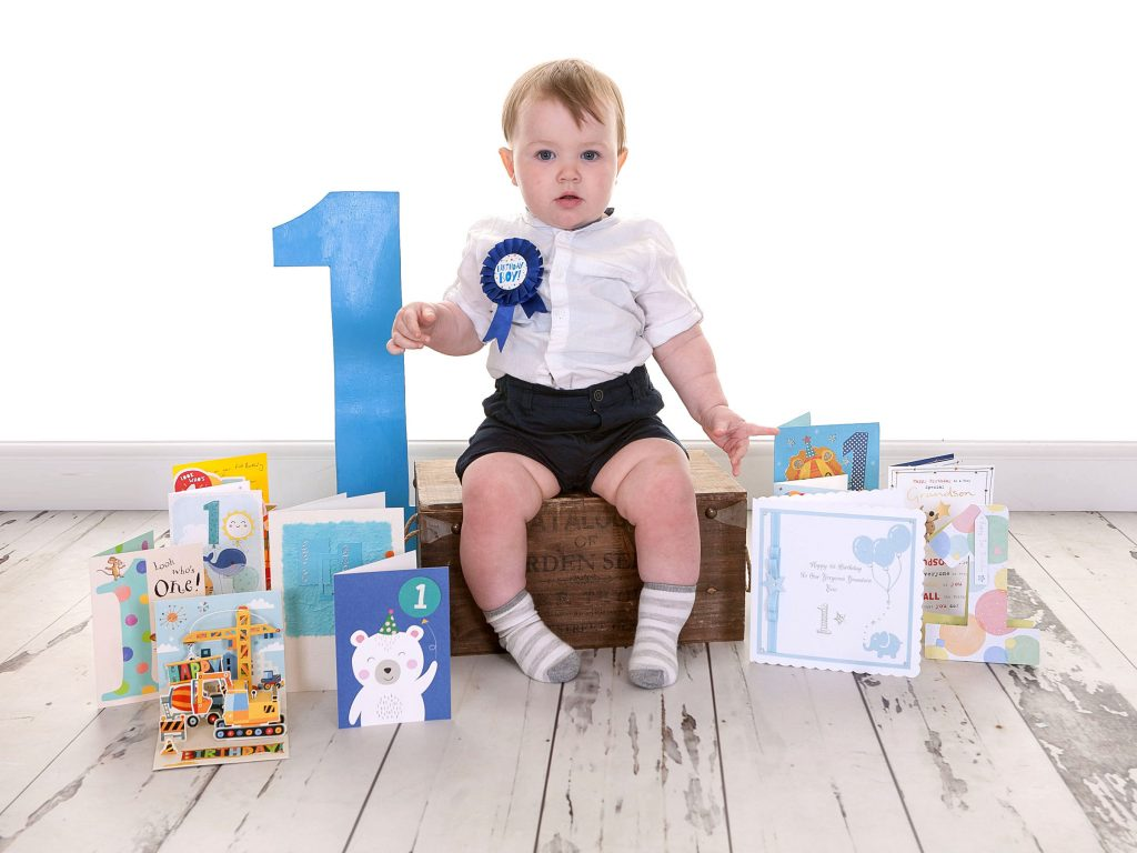 1st birthday - boy sat on crate surrounded by birthday cards
