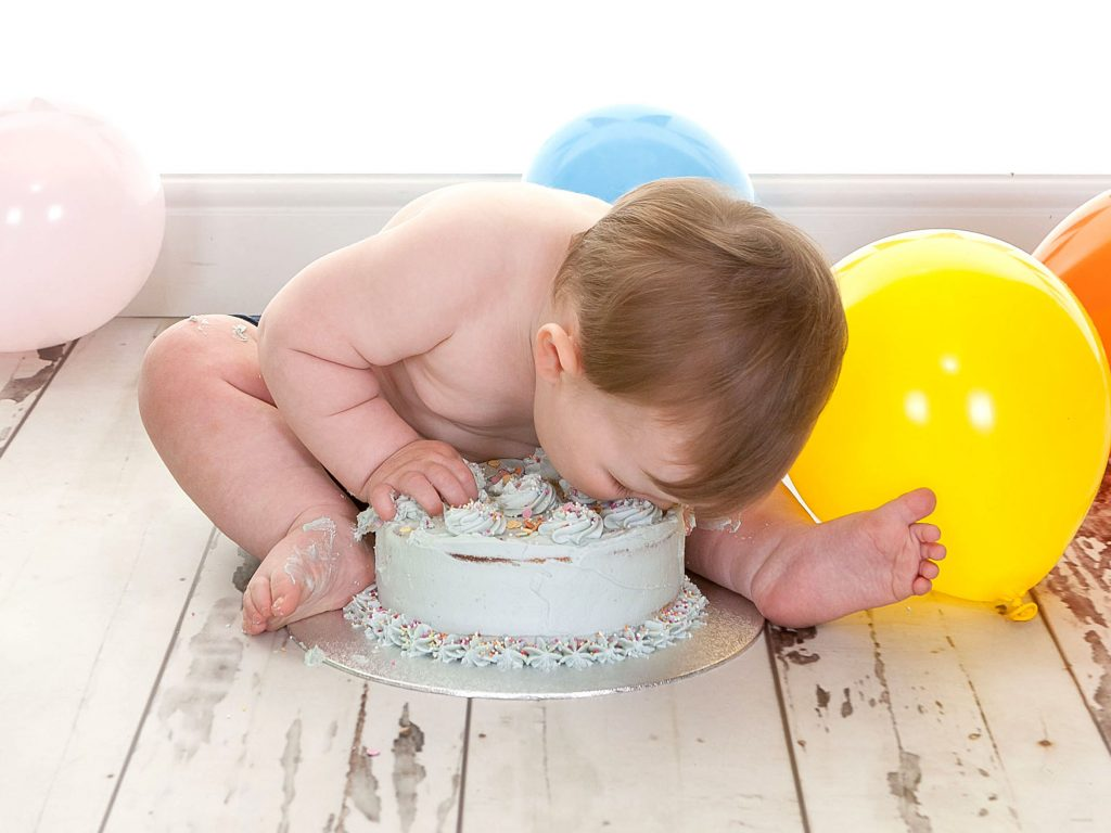 Little boy with his head in a birthday cake
