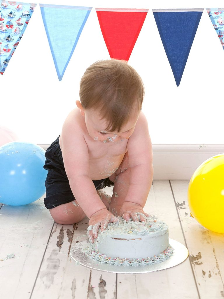 Little boy grabbing all the soft icing off a birthday cake
