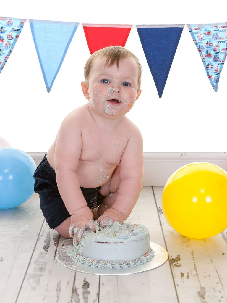 Little boy with his hands stuck into a birthday cake