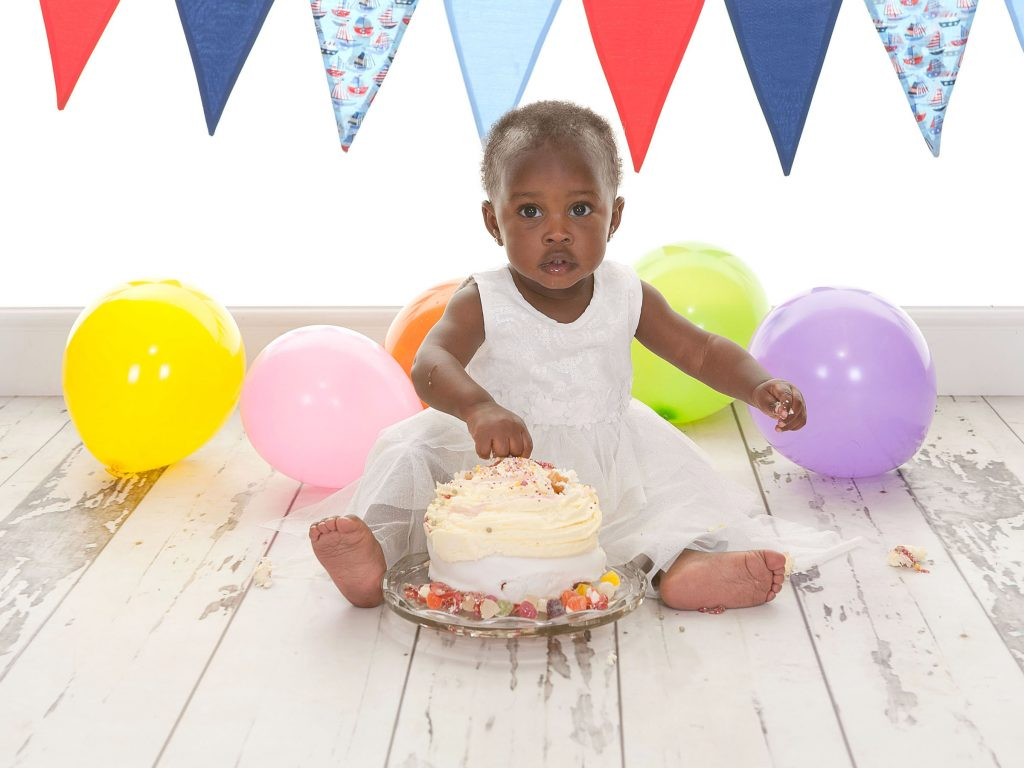 Little girl surrounded by banners and balloons about to smash her cake