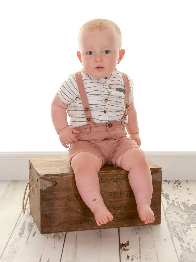 little boy in smart dungarees sat on an old style crate