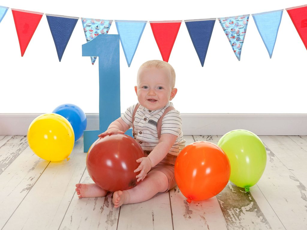 Little baby enjoying their first birthday photo session holding a balloon