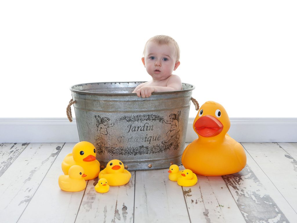 Little baby in an antique bath tub surrounded by yellow ducks